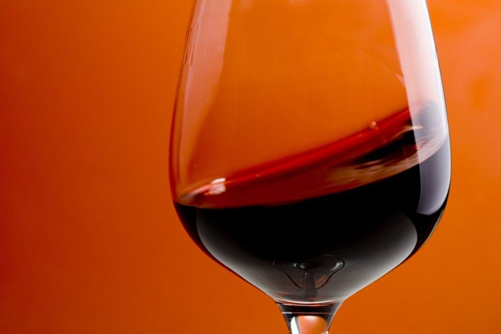 Красное вино на фоне оранжевого интерьера